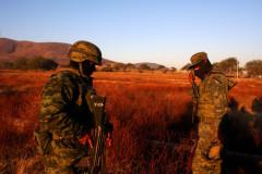 Militares esperan instrucciones antes de entrar a un rancho donde se procesaban drogas químicas.