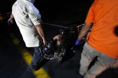 Rescatistas cargan el cuerpo de un hombre que murió calcinado al quedar atrapado en medio de un enfrentamiento entre sicarios.