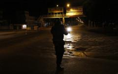 Un policía federal apunta a un auto sospechoso al término de un enfrentamiento con narcotraficantes en Ciudad Guzmán, Jalisco.
